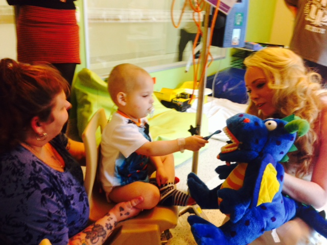 Three-year-old Stephen walked the corridors for the first time in two weeks to see the Tooth Fairy. He helped brush Boris the Dragon's Teeth.